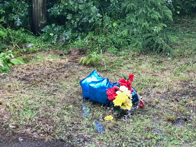 Flowers and balloons mark the location where the body of homicide victim William C. Balfour Sr., 70, was found July 2 along Blaine Street, south of Centennial Avenue.