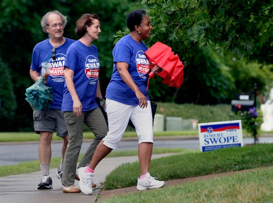 Nashville mayoral candidate Carol Swain, right, walks with campaign volunteers Colin Stimpert, left, and Julianne Curtis as they walk from house to house hoping to get votes in Swain's neighborhood on Saturday, June 22, 2019, in Nashville, Tenn.