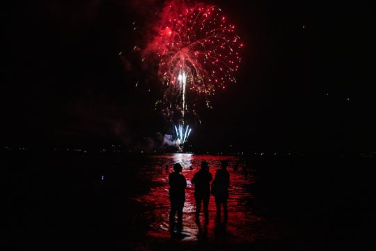 Families gather for a firework show in celebration of Independence Day at Naples Pier on Thursday, July 4, 2019.