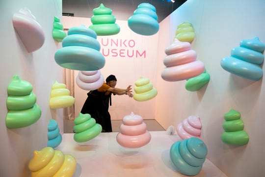 In this Tuesday, June 18, 2019, photo, a woman jokingly poses with large poop-shaped figurines at the Unko Museum in Yokohama, south of Tokyo. In a country known for its cult of cute, even poop is not an exception. A pop-up exhibition at the Unko Museum in the port city of Yokohama is all about unko, a Japanese word for poop. The poop installations there get their cutest makeovers. They come in the shape of soft cream, or cupcake toppings. (AP Photo/Jae C. Hong)