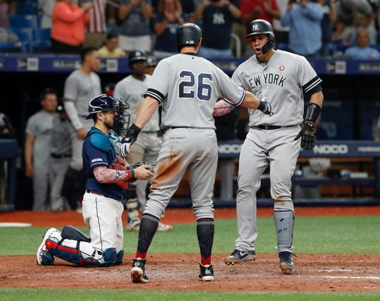 New York Yankees' Gary Sanchez, right celebrates with teammate DJ LeMahieu after hitting a three-run home run against the Tampa Bay Rays during the 10th inning of a baseball game Thursday, July 4, 2019, in St. Petersburg, Fla.