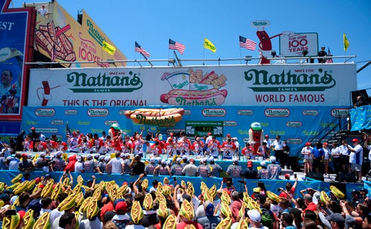 Men compete at eating as many hot dogs as possible in ten minutes during the 2019 Nathan's Famous Fourth of July hot dog eating contest on Coney Island on July 4, 2019 in New York.