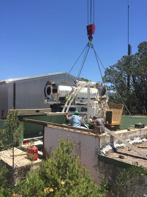 A 75-ton crane extracts Telescope IV from its resting place since 1948. The building roof has been rolled back to expose it, as it is on rails.
