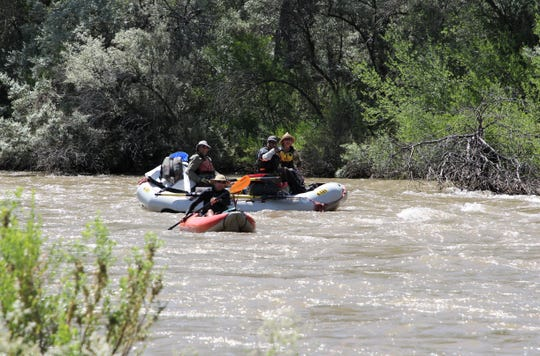 People float down the Animas River on a raft and kayak, Friday, July 5, 2019, in Farmington.
