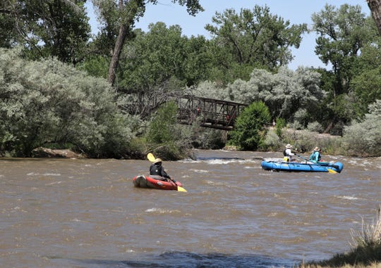 People float through Berg Park on the Animas River on a raft and kayak, Friday, July 5, 2019, inFarmington.