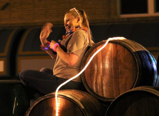 A rider waves to the crowd while sitting on a barrel loaded on the St. Clair Winery float in the July 4 Farmington Rotary Electric Light Parade.