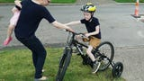 Colin Schrader tries out his new bike to help him get around his Birmingham neighborhood. The six year old has a mild case of cerebral palsy.