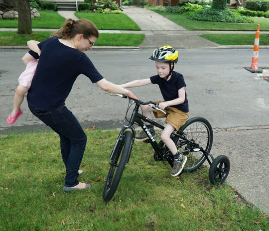 Erin Schrader, holding daughter Kate, 3, helps her son Colin, 6, power out of a lawn obstacle as he tries out his more-than-kid-sized training wheel bike gift from Beaumont Hospital.