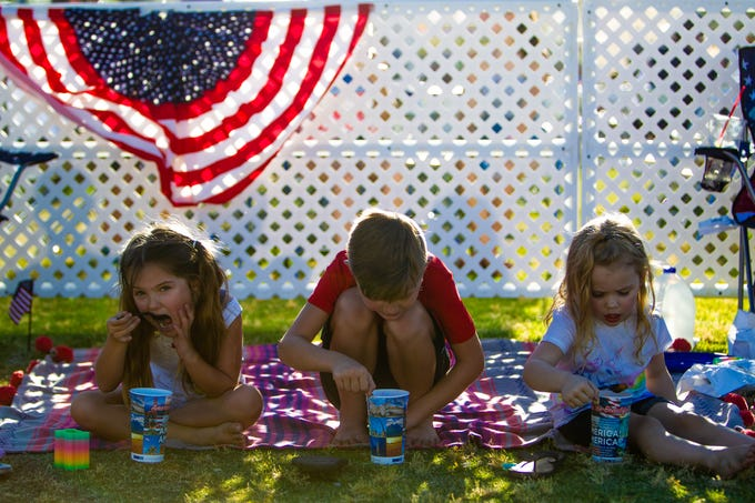 Siblings Olivia Lewis, Declan Lewis and Emmy Cox (from left) eat snow cones at Tempe Town Lake while they wait for fireworks on July 4, 2019.