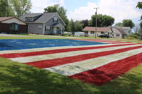 J.R. Majewski said he wanted to honor veterans by painting this giant American flag in his front yard.