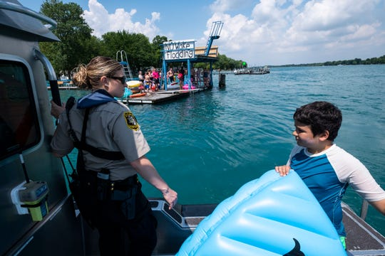 St. Clair County Sheriff Marine Deputy Jessica Verwys, left, stands on the rear deck of a patrol boat with Josiah Khaliaha, 11, after pulling him from the St. Clair River Thursday, July 4, 2019. Josiah was found struggling against the current of the river and was rescued by deputies.