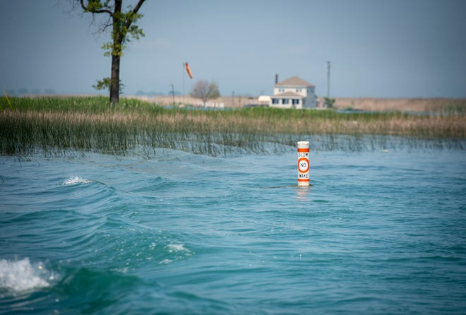 A buoy marking a no-wake zone floats in a channel off the St. Clair River in Clay Township. No-wake zones have been set up along the river to help prevent damage from the high water.