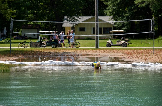 A young boy plays in the water near a flooded volleyball court Thursday, July 4, 2019, at a park on Russell Island.
