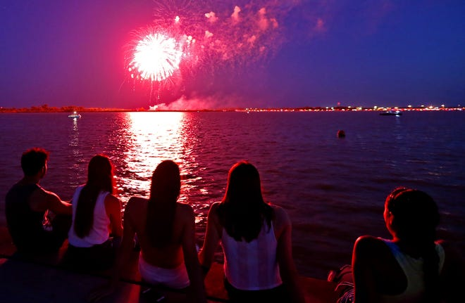 A group of young people watch the 4th of July fireworks display over Lake Nasworthy on Thursday.