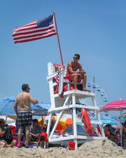 Christian Ellis, a first year member of the Ocean City Beach Patrol, keeps watch over the inlet beach on July 4, 2019.