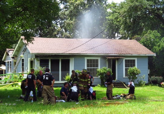 Shreveport fire fighters cool off outside while fighting a fire at a home in the 4500 block of Lyba Street on Friday, July 5, 2019.