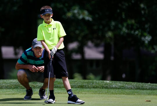 Landon Nichols and his dad Scott line up a putt on the first green of Fremont Hills Country Club on Wednesday, July 3, 2019.