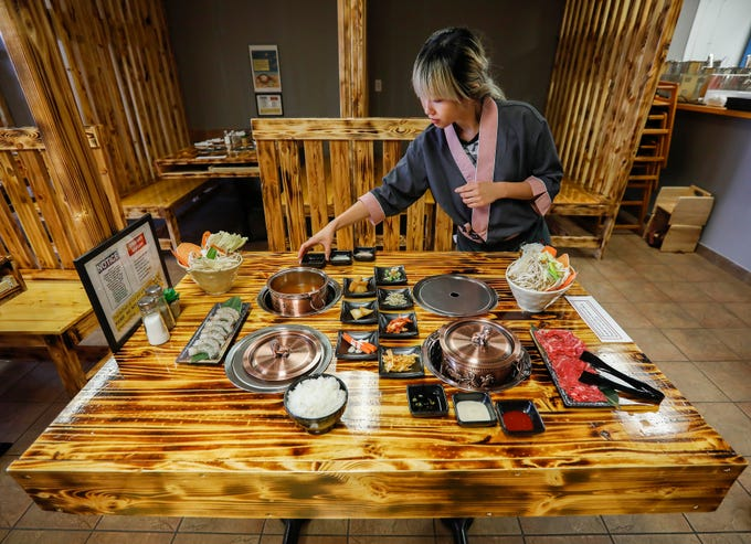 Stephanie Liu, the manager at Little Korea, sets out sauces to go along with the hot pot on Friday, July 5, 2019. The new restaurant is located at 3354 S. National Ave. in Springfield, Mo.