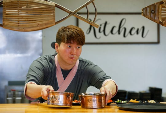 "Owner Hong ""Jay"" Jung sets out two bowls of broth for service at Little Korea, a new restaurant located at 3354 S. National Ave. in Springfield, Missouri."
