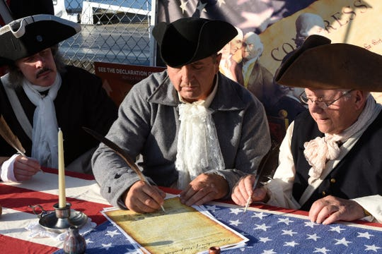 Community members portraying the founding fathers prepare to reenact the signing of the Declaration of Independence, Thursday, July 4, 2019 at Hester Park.