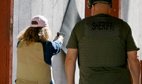 In this Saturday, June 29, 2019, photo, Cindy Bullock, Timpanogos Academy secretary, participates in shooting drills at the Utah County Sheriff's Office shooting range during the teacher's academy training in Spanish Fork Canyon, Utah. About 30 teachers in Utah are spending their summer learning how to stuff wounds and shoot guns as part of a training held by police to prepare educators for an active shooter scenario in their schools.
