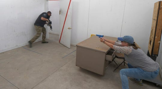 In this Saturday, June 29, 2019, photo, Christy Belt, Timpanogos Academy 5th grade teacher, engages in an exercise designed to help teachers make good decisions in critical, high-stress situations such as an active shooter incident during the teacher's academy training at the Utah County Sheriff's Office shooting range, in Spanish Fork Canyon, Utah.