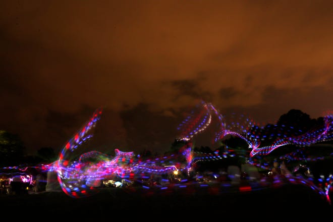 A long exposure photograph of three young boys chasing each other with a sword lit up with red, white, and blue lights at Tom Brown Park while waiting for the Fourth of July fireworks show. The colorful display was later cancelled due to a storm.