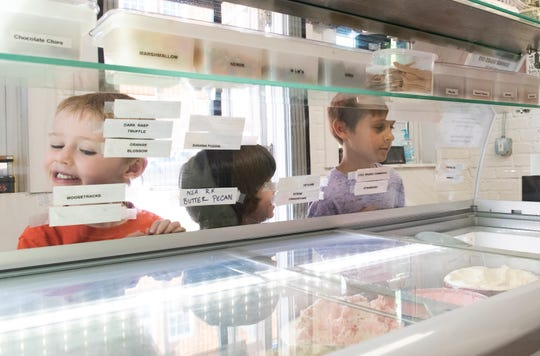 From left, Zachary Garrett, 5, Daniel McFarland, 4, and Cameron Forbes, 7, order ice cream at Mama Rae's Scoops on the Square in Pendleton.