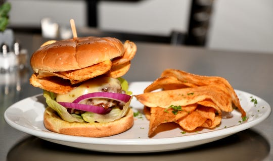 "Table 57's signature dish, the $14 ""Table 57 Burger,"" features house-made potato chips for a surprising crunch."