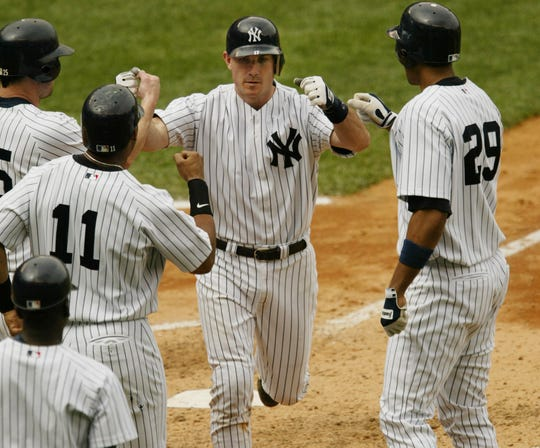 New York Yankees John Flaherty crosses the plate to greet teammates Jason Giambi, left, Gary Sheffield, second from left, and Tony Clark, right, after hitting a sixth inning grand slam off Colorado Rockies pitcher Scott Dophmann , Thursday, June 10,  2004, at New York's Yankee Stadium.