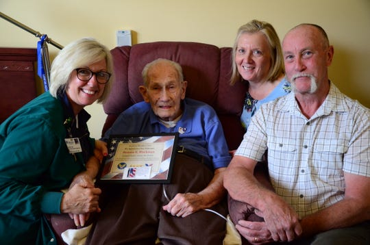 Ben Workman, a World War II veteran, is shown with Heidi Williams, Genesis Hospice Care, left, and son, Paul and daughter-in-law, Pam Workman.