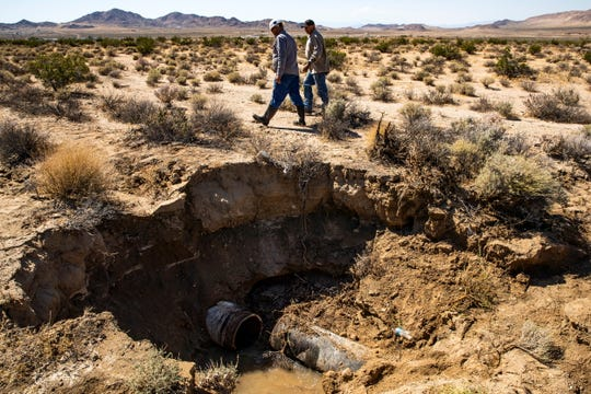 Workers walk by a crater formed by the explosion of a water pipe due to the tremors of an earthquake near Ridgecrest, Calif. on July 4, 2019.
