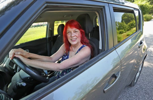 Jane Reed sits in her Kia in Holliday Park, Friday, July 5, 2019.  The Indianapolis resident and special education advocate drives a lot around Indiana and loves her car.  She does not want a Tesla, though, because she doesn't trust Elon Musk.  She also worries about her safety in a Tesla, if she were hit by another vehicle.