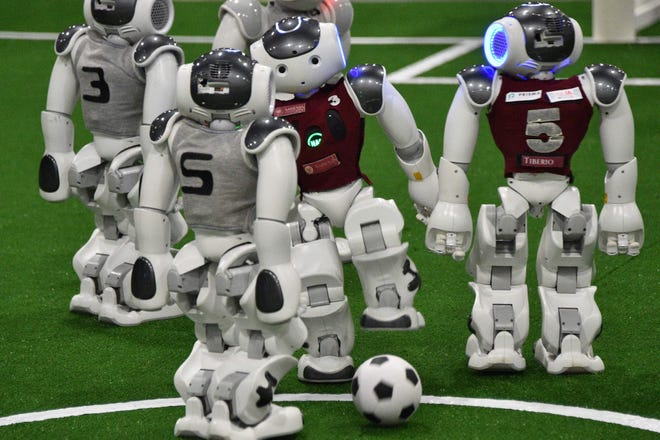 Robots play football at the RoboCup 2019 event in Sydney on July 4, 2019. About 170 teams from more than 30 countries gathered in Sydney for the annual RoboCup event which sees robot soccer teams go head to head in an event designed to enhance development of artificial intelligence and robotics.