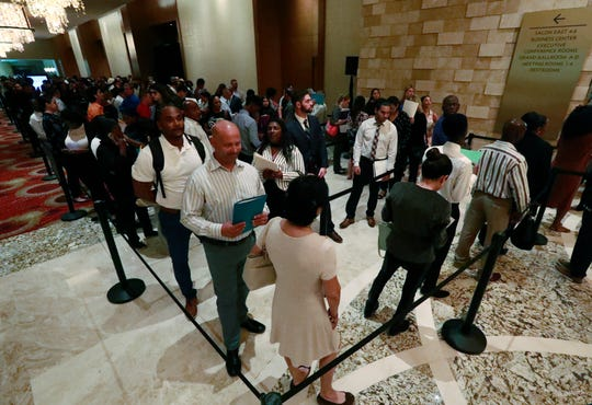 Job applicants line up at the Seminole Hard Rock Hotel & Casino Hollywood during a job fair in Hollywood, Florida.