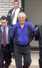 File photo taken in 2002 shows Peter Gotti (center) the brother of the late Gambino crime family boss John Gotti, being escorted out of the Waterfront Commission.  (AP Photo/New York Daily News, Mike Albans)