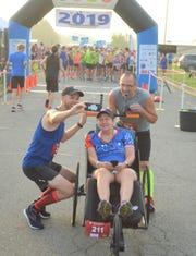 Longtime runner Sue Read, who now suffers from a rare disease called GSS, was able to get back on the course in the Battle Creek Half Marathon with the use of a donated racing chair and the help of Dave Proulx (with camera) and Jim Petersen (bib No. 194), who pushed her during the race.