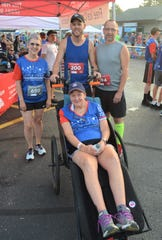 Longtime runner Sue Read, who now suffers from a rare disease called GSS, was able to get back on the course in the Battle Creek Half Marathon with the use of a donated racing chair and the help of Dave Proulx (holding chair) and Jim Petersen (bib No. 194), who pushed her during the race, as well as Kim Clifford, left, who helped organize a GoFundMe page.