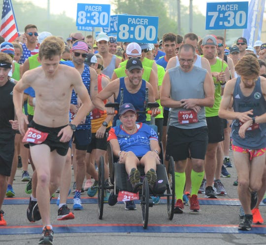 Longtime runner Sue Read, who now suffers from a rare disease called GSS, was able to get back on the course in the Battle Creek Half Marathon with the use of a donated racing chair and the help of Dave Proulx (holding chair) and Jim Petersen (bib No. 194), who pushed her during the race.
