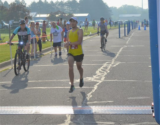 Daniel Garza, of Dearborn, crosses the finish line to win the Battle Creek Half Marathon on Saturday.