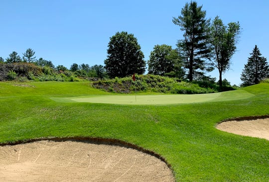 The green of Rutland Country Club's par-3 third hole is wedged between bunkers on the right and rock outcroppings on the left.