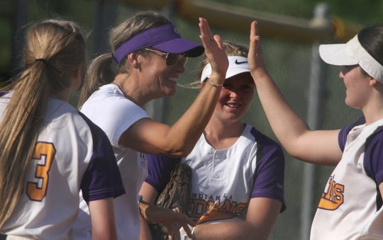 Indianola head coach Stacy Evans greets her players as they return from the field. Indianola beat Urbandale 10-0 in the first game of a July 2 doubleheader in Indianola.