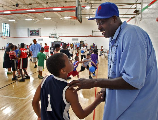 Late Drake basketball star Lewis Lloyd talks with a basketball camper in 2013.