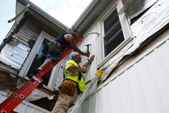 Homeowner Rich Fetters and volunteer Bob Ball put siding on the Salem Avenue house on July 6.
