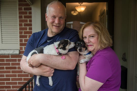 Craig Berg poses for a photo with Minnie as his wife, Debbie, carries their newly adopted dog Honey (they plan to change his name to Henri) at their home in Royal Oak on Saturday, July 6, 2019.