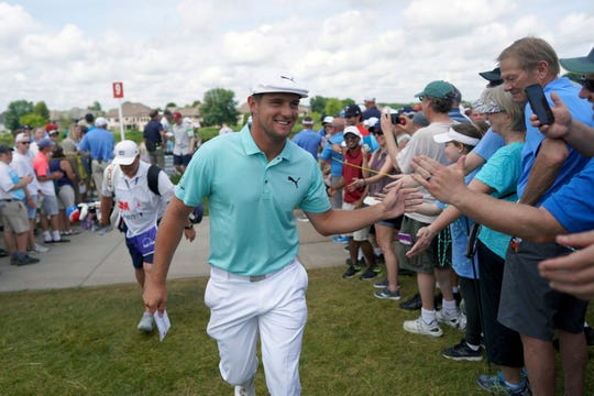 Bryson DeChambeau greets fans as he leaves the ninth hole during the second round of the 3M Open on Friday.