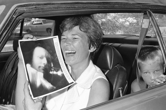 Mrs. Jan Armstrong registers pleasure over a picture of her husband, Apollo 11 commander, Neil Armstrong, taken during a telecast from the spacecraft and beamed back to earth, July 18, 1969. In the rear seat is son, Mark, 6.
