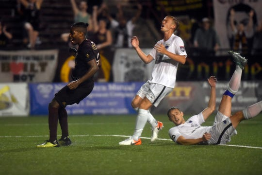 Detroit City FC forward Shawn Lawson, left, beats two Grand Rapids FC defenders and scores a goal to tie the game 1-1 in the second half Friday.