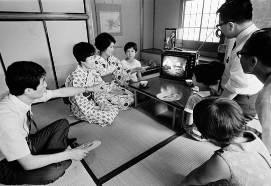 A family in Tokyo watches their TV screen, where President Richard Nixon is superimposed on a live TV broadcast of the Apollo 11 astronauts' salute from the moon, July 21, 1969.