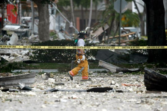 A firefighter walks through the remains of a building after an explosion on Saturday, July 6, 2019, in Plantation, Fla.